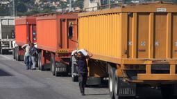 Seorang pria membawa sekarung jagung yang dicuri dari truk di luar pelabuhan di Puerto Cabello, Venezuela, Selasa (23/1). Inflasi yang mencapai 2.600 persen berakibat pada mata uang Venezuela tidak lagi bernilai di masyarakat. (AP Photo/Fernando Llano)
