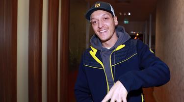 Gelandang Jerman, Mesut Ozil tersenyum saat kedatangannya di Bandara Ataturk di Istanbul (18/1/2021). Ozil akhirnya meninggalkan Arsenal dan bergabung dengan klub asal Turki, Fenerbahce. (AFP/Fenerbahce.Org)