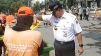 Gubernur DKI Jakarta, Anies Baswedan memeriksa kondisi tempat sampah saat membantu membersihkan sisa residu gas air mata dari badan jalan MH Thamrin dekat Gedung Bawaslu, Jakarta, Kamis (23/5/2019). (Liputan6.com/Helmi Fithriansyah)
