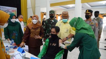 Gubenrur Gorontalo Rusli Habibie bersama ketua TP PKK dan unsur Forkopimda menyaksikan penyuntikan vaksin covid-19 kepada salah satu pengemudi ojok online (Arfandi Ibrahim/Liputan6.com)