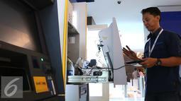 Teknisi memperbaiki mesin ATM di Jakarta, Selasa (27/9). Periode konversi diberikan BI untuk mengganti teknologi kartu ATM menjadi cip hingga tahun 2021. (Liputan6.com/Angga Yuniar)