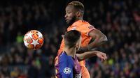 Pemain Olympique Lyon Moussa Dembele berebut bola dengan pemain Barcelona, Clement Lenglet pada leg kedua 16 besar Liga Champions di Camp Nou, Rabu (13/3). Barcelona menaklukkan Olympique Lyon dengan skor telak 5-1. (AP/Emilio Morenatti)