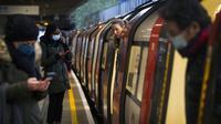 Para penumpang naik kereta Bawah Tanah Jubilee Line di Stasiun Canning Town selama jam sibuk di London, Inggris, 12 Januari 2021. Inggris sedang menerapkan lockdown nasional ketiga untuk mengekang penyebaran virus corona COVID-19. (Victoria Jones/PA via AP)