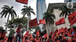 Massa buruh mengibarkan bendera saat aksi menolak UU Cipta Kerja di kawasan Patung Kuda, Jakarta, Selasa (10/11/2020). Massa buruh juga memperingati para pahlawan dari kelas pekerja yang telah gugur memperjuangkan haknya. (merdeka.com/Iqbal S. Nugroho)