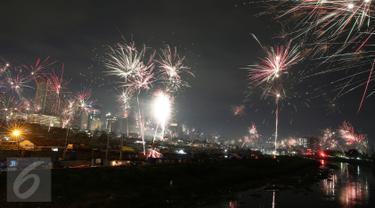 Tampak kembang api menghiasi langit Jakarta saat malam pergantian tahun di kawasan Banjir Kanal, Petamburan, Jakarta, Minggu (01/1). (Liputan6.com/Johan Tallo)
