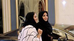 Dua wanita Saudi saat mengunjungi pameran mobil di resor Jeddah Laut Merah Jeddah (5/10). Pada bulan September 2017 Kerajaan Arab Saudi mengeluarkan dekrit yang memperbolehkan wanita untuk mengendarai mobil. (AFP Photo/Amer Hilabi)