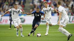 Penyerang Prancis, Kylian Mbappe, berusaha melewati pemain Jerman pada laga UEFA Nations League di Stade de France, Paris, Selasa (16/10/2018). Prancis menang 2-1 atas Jerman. (AP/Christophe Ena)