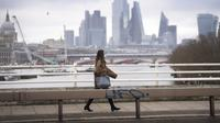 Seorang wanita yang mengenakan masker berjalan di atas Waterloo Bridge yang kosong, London, Inggris, 12 Januari 2021. Inggris sedang menerapkan lockdown nasional ketiga untuk mengekang penyebaran virus corona COVID-19. (Victoria Jones/PA via AP)