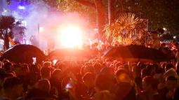 Ribuan suporter Skotlandia berkumpul dan menyalakan flare di Leicester Square di London, Jumat (18/6/2021). (AP/Alberto Pezzali)