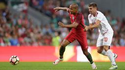 Gelandang Portugal, Joao Mario, melewati pemain Gibraltar, Liam Walker. Juara Eropa 2016 itu menguasai jalannya laga dengan penguasaan bola sebesar 86 persen. (Reuters/Miguel Vidal)