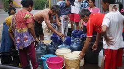 Warga mengisi air bersih ke dalam galon, jeriken, dan ember di kawasan Cipayung, Jakarta Timur, Rabu (20/11/2019). Warga memanfaatkan bantuan air bersih dari Pemprov DKI Jakarta untuk memenuhi kebutuhan sehari-hari. (Liputan6.com/Immanuel Antonius)