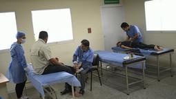 Petugas kesehatan melakukan perawatan pemulihan pasien terpapar virus Corona COVID-19 di pusat kesehatan yang dikelola pemerintah di lingkungan Coche di Caracas, Venezuela pada 25 Februari 2021. (AP Photo / Matias Delacroix)
