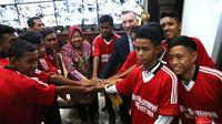 Supriadi diapit Wali Kota Surabaya Tri Rismaharini dan Wakil Wali Kota Liverpool, Gary Miller, Sabtu (17/11/2018), di Balai Kota Surabaya. (Bola.com/Zaidan Nazarul)