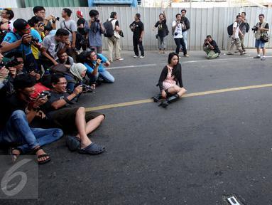 Para fotografer melakukan pemotretan seorang model di Jalan MH Thamrin, Jakarta, Minggu (19/7/2015). Momen Jakarta sepi akibat banyak yang mudik, dimanfaatkan fotografer untuk memotret model. (Liputan6.com/Johan Tallo)