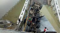 Jembatan Widang Tuban ambruk, truk teperosok mengimpit seorang pengendara motor. (Liputan6.com/Dok.BNPB)