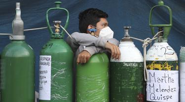Seorang pemuda bersandar pada tabung oksigennya yang kosong saat menunggu toko isi ulang dibuka di lingkungan San Juan de Lurigancho di Lima, Peru, Senin (22/2/2021). Kekurangan oksigen medis untuk merawat pasien COVID-19 terus menjadi norma nasional. (AP Photo/Martin Mejia)