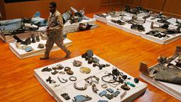 Perwira militer melewati puing-puing rudal dan drone yang digunakan dalam serangan kilang minyak Aramco pada konferensi pers di Riyadh, Arab Saudi, Rabu (18/9/2019). Kendati pemberontak Houthi Yaman mengklaim serangan itu, Amerika Serikat menuduh Iran berada di belakangnya. (AP Photo/Amr Nabil)