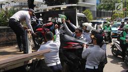 Petugas Dishub DKI Jakarta mengangkut motor saat razia parkir liar di Jalan KH Wahid Hasyim, Jakarta, Rabu (4/4). Dishub DKI Jakarta menertibkan pengendara ojek online yang memarkirkan kendaraan sembarangan di pinggir jalan. (Liputan6.com/Arya Manggala)
