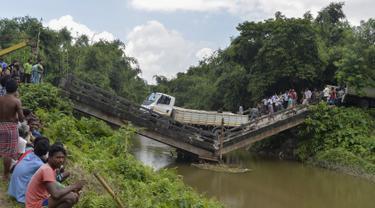 Penduduk desa berkumpul di dekat jembatan yang roboh di desa Phasidewa dekat perbatasan India-Bangladesh di pinggiran Siliguri di negara bagian India, Bengal Barat (7/9). Tidak ada korban dalam kejadian jembatan roboh tersebut. (AFP Photo/Diptendu Dutta)