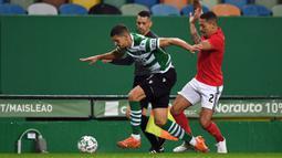 Bek Sporting Lisbon, Zou (kiri) menguasai bola dibayangi bek Benfica, Gilberto Junior dalam laga lanjutan Liga Portugal 2020/21 di Jose Avalade Stadium, Lisbon, Senin (1/2/20201). Sporting menang 1-0 atas Benfica. (AFP/Patricia De Melo Moreira)