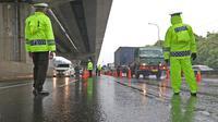 Petugas kepolisian berjaga di Pos Penyekatan Jalur Mudik di Gerbang Tol Cikarang Barat, Kabupaten Bekasi, Senin (18/5). Memasuki H-6 Lebaran, puluhan kendaraan diminta untuk putar balik karena melanggar larangan mudik sebagai upaya memutus rantai penyebaran Covid-19. (Liputan6.com/Herman Zakharia)