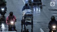 Pedagang melintas saat hujan mengguyur Jakarta, Senin (26/10/2020). BPBD DKI Jakarta mengeluarkan peringatan dini cuaca berupa potensi terjadinya hujan lebat disertai petir dan angin kencang dampak dari siklon tropis Molave hingga 27 Oktober 2020. (merdeka.com/Iqbal S. Nugroho)