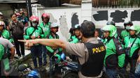 Petugas saat memberikan arahan kepada pengemudi Go-Jek yang diamankan di kawasan Senayan, Jakarta Pusat, Selasa (22/3). Mereka diamankan karena diduga akan melakukan aksi balasan terhadap Sopir Taksi.(Liputan6.com/Fery Pradolo)