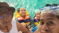 Andik Vermansah bersama kedua orangtuanya, Saman (ayah) dan Jumaiyah (ibu), menikmati wisata pantai Lombok dengan aktivitas menyelam. (Bola.com/Dok. Pribadi)