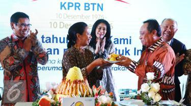 Menteri BUMN Rini M Soemarno memberi tumpeng kepada Dirut Bank BTN, Maryono saat acara HUT KPR BTN di Menara BTN, di Jakarta Selasa (14/12). Perayaan ditandai dengan pemotongan tumpeng oleh Rini. (Liputan6.com/Angga Yuniar)