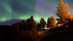 Pancaran cahaya aurora borealis menghiasi Desa Erikslund di Vasternorrland County, Swedia (23/8). Fenomena alam yang indah ini terjadi pada bulan Maret-April dan September-Oktober. (AFP PHOTO/ JONATHAN NACKSTRAND)