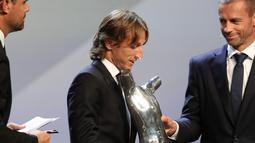 Gelandang Real Madrid asal Kroasia, Luka Modric menerima piala pemain terbaik UEFA dari presiden UEFA Aleksander Ceferin di The Grimaldi Forum di Monaco, (30/8). Modric mengalahkan Cristiano Ronaldo dan Mohamed Salah. (AFP Photo/Valery Hache)