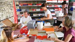 Relawan asosiasi Goupil memberi makan sejumlah hewan di Rumah Sakit Margasatwa di Laroque, Prancis, Selasa (9/7/2019). Goupil merawat ratusan hewan terdampak gelombang panas yang melanda Prancis dan Eropa sejak akhir Juni. (SYLVAIN THOMAS/AFP)