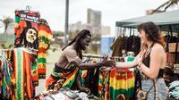 Penggemar musik reggae saling sapa saat memperingati ulang tahun Bob Marley dalam One Love Festival and Rasta Fair di North Beach Amphitheatre, Durban, Afrika Selatan, Minggu (3/2). (RAJESH JANTILAL/AFP)