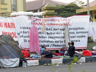 Sejumlah pencari suaka mendirikan tenda di trotoar depan gedung bekas Markas Kodim, Kalideres, Jakarta, Selasa (3/9/2019). Pemprov DKI Jakarta memberikan batas waktu hingga 31 Agustus 2019, namun masih banyak pencari suaka memilih bertahan di gedung itu. (Liputan6.com/Helmi Fithriansyah)