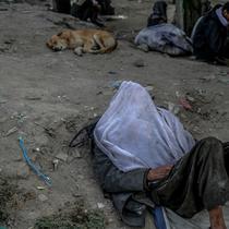 Seorang pria tidur di pinggir jalan saat orang lain mengonsumsi narkoba di Kabul,  Afghanistan, 21 September 2021. Afghanistan dikenal sebagai penghasil opium nomor satu di dunia. (BULENT KILIC/AFP)