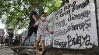 Pejalan kaki melintas di depan mural di Jalan Raya Citayam, Depok, Jawa Barat, Rabu (25/8/2021). Mural tersebut merupakan wujud ekspresi dari sejumlah seniman serta sebagai media penyampaian kritik sosial kepada pemerintah di tengah pandemi COVID-19. (Liputan6.com/Herman Zakharia)