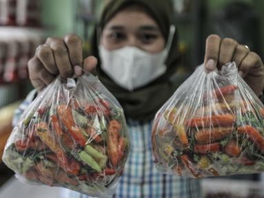 Pekerja memperlihatkan paket cabai rawit dalam Pasar Cabai Murah di Pasar Mitra Tani Klender, Duren Sawit, Jakarta, Rabu (10/3/2021). Dalam rangka menekan harga cabai di pasar, Kementan menggelar Pasar Cabai Murah di 34 lokasi Jakarta, Bogor dan Bekasi mulai 8-20 Maret. (merdeka.com/Iqbal S Nugroho)