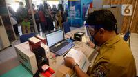 Petugas melayani warga yang akan melakukan pencetakan di mesin Anjungan Dukcapil Mandiri (ADM) di Pamulang Square, Tangerang Selatan, Senin (15/9/2020). Pemkot Tangsel memudahkan pelayanan kependudukan untuk membuat KTP El, Kartu Identitas Anak dan Kartu Keluarga. (merdeka.com/Dwi Narwoko)