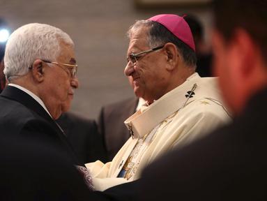 Presiden Palestina Mahmoud Abbas (kiri) berjabat tangan dengan pendeta saat menghadiri misa Natal di Gereja Nativity, Bethlehem, Jumat ( 25/12/2015). Presiden Abbas berharap cita-citanya mewujudkan perdamaian di Palestina bisa. (REUTERS /Fadi Arouri )