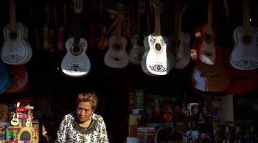 """Seorang wanita menjual replika gitar dari film """"Coco"""" di kiosnya di Paracho, Meksiko (8/1). Kerena kepopuleran film animasi Coco pengrajin di Meksiko dibanjiri pesanan gitar yang mirip di film tersebut. (AFP Photo/ Ronaldo Schemidt)"""
