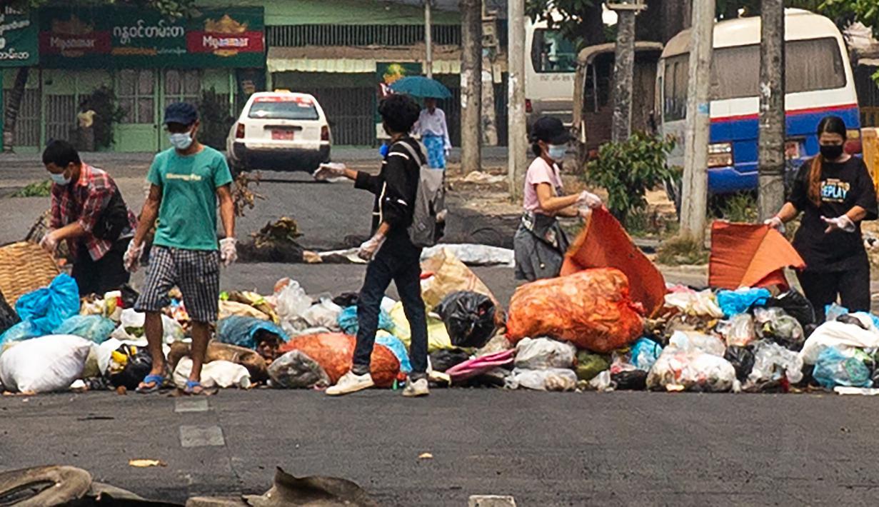 """Pengunjuk rasa membuang sampah di jalan untuk membentuk barikade darurat selama demonstrasi menentang kudeta militer di kota Thaketa Yangon, Myanmar, Selasa (30/3/2021). """"Serangan sampah"""" menjadi taktik baru pengunjuk rasa Myanmar untuk melawan junta militer. (AFP/FACEBOOK)"""