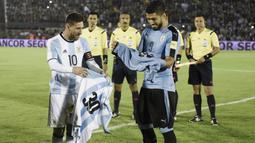 Lionel Messi dan Luis Suarez bertukar jersey sebelum laga kualifikasi Piala Dunia 2018 antara Argentina melawan Uruguay di Montevideo, Uruguay, (31/8/2017). Argentina bermain imbang 0-0. (AP/Matilde Campodonico)