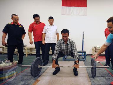 Menpora Imam Nahrawi (keempat kiri) bersiap melakukan angkatan saat meninjau kesiapan akhir atlet angkat besi di PB PABBSI, Jakarta, Selasa (21/6). Tujuh atlet angkat besi akan berlaga di Olimpiade Rio 2016. (Liputan6.com/Helmi Fithriansyah)
