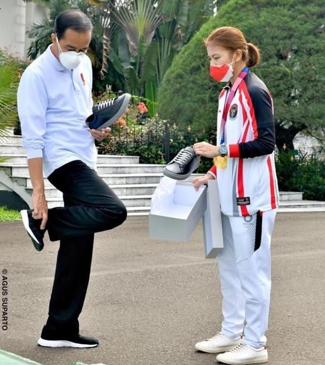 Presiden Jokowi mencoba sepatu buatan dalam negeri yang merupakan produk usaha dari atlet bulu tangkis peraih medali emas Olimpiade Tokyo 2020, Greysia Polii. (sumber: Instagram @jokowi)