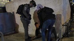 Polisi Israel menahan pemuda Palestina di Gerbang Damaskus ke Kota Tua Yerusalem di kompleks Masjid Al-Aqsa (7/6/2021). Layanan ambulans Bulan Sabit Merah Palestina mengatakan 88 orang Palestina yang terluka dibawa ke rumah sakit setelah terkena peluru logam berlapis karet. (AP Photo/Mahmoud Illean)