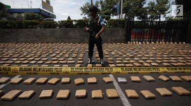 Petugas berjaga saat rilis barang bukti ganja sebanyak 1.300 paket dengan total 1,3 ton di Polres Jakarta Barat, Kamis (4/1). Polres Metro Jakbar berhasil menghentikan penyelundupan 1,3 ton ganja dari Provinsi Aceh ke Jakarta. (Liputan6.com/Arya Manggala)