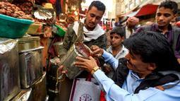 Seorang pembeli melihat kurma yang dijajakan oleh pedagang di sebuah pasar di kota tua Sanaa, Sabtu (11/5/2019). Buah kurma sangat identik saat bulan suci Ramadan, malah menjadi makanan wajib saat berbuka puasa. (Photo by Mohammed HUWAIS / AFP)