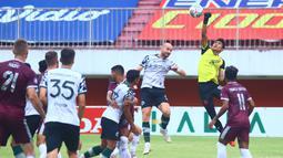 Kiper PSM Makassar, Hilman Syah (kanan) mencoba menghalau bola dari ancaman pemain Persikabo 1973, Veniamin Shumeyko dalam laga pekan ke-9 BRI Liga 1 2021/2022 di Stadion Maguwoharjo, Sleman, Selasa (26/10/2021). (Bola.com/Nandang Permana)