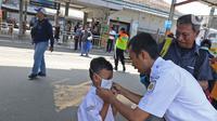 Petugas memasangkan masker ke seorang anak saat sosialisasi pencegahan virus  corona yang digelar PT KAI Daop 1 melalui Rail Clinic  di stasiun kereta Depok, Jumat (6/3/2020).  (Liputan6.com/Herman Zakharia)