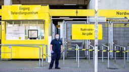 Petugas keamanan mengenakan masker berjaga-jaga di luar pusat pengujian COVID-19 di stadion milik Borussia Dortmund di Jerman (4/4/2020). Kamar-kamar di tribun utara Stadion Westfalen dipersiapkan untuk menampung orang-orang yang diduga terinfeksi COVID-19. (Xinhua/Joachim Bywaletz)